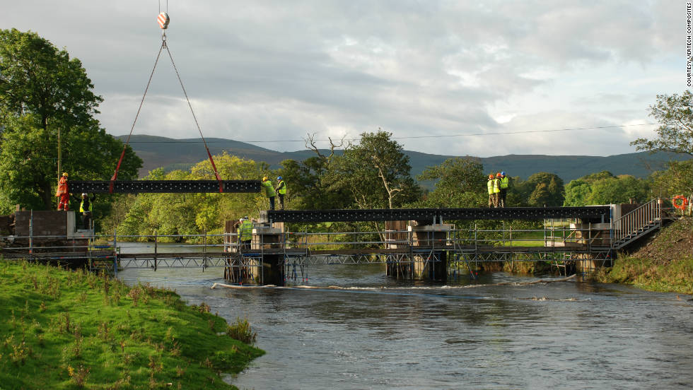 Third main beam of bridge made from recycled plastic is lowered into position by crane.